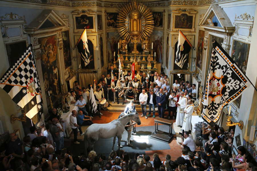 July 2, 2013. Supporters of the Contrada of Wolf attend a horse-blessing ceremony in the church of Saint Rocco prior the Palio horse race in Siena, Italy. The Palio medieval race is held twice a year in Siena with jockeys riding bareback around a makeshift race course set up in the city's central square.
